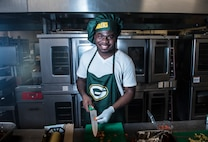 "U.S. Army Specialist Kevron Usher, culinary specialist with Task Force Talon's  E Battery, 3rd Air Defense Artillery Regiment, pauses for a photo March 8, 2018, at Magellan Inn Dining Facility, Guam. Usher joined Airmen in the quarterly ""Top Chef Competition"" at Magellan Inn and sported his Green Bay Packers cooking gear in celebration of the occasion. (U.S. Air Force photo by Staff Sgt. Alexander W. Riedel)"