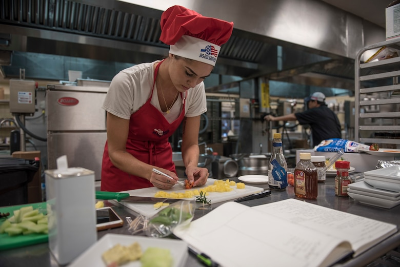 """U.S. Air Force Senior Airman Caroline Spellen, 36th Force Support Squadron food services supervisor, cuts a cherry tomato into a decorative flower March 8, 2018, at Magellan Inn Dining Facility, Guam. Spellen won the quarterly """"Top Chef Competition"""" at Magellan Inn, which tasked military cooks to create interesting dishes with mandatory ingredients provided in a """"mystery box."""" (U.S. Air Force photo by Staff Sgt. Alexander W. Riedel)"""