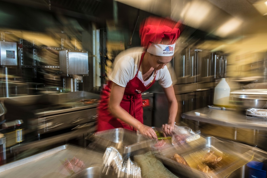 """U.S. Air Force Senior Airman Caroline Spellen, 36th Force Support Squadron food services supervisor rushes to prepare a dish during a """"Top Chef"""" competition March 8, 2018, at Magellan Inn Dining Facility, Guam. Spellen won the quarterly challenge, which tasked Air Force and Army cooks to serve a creative dish with mandatory ingredients provided in a """"mystery box."""" (U.S. Air Force photo by Staff Sgt. Alexander W. Riedel)"""
