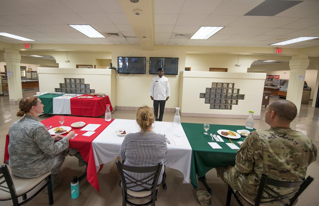 At front, U.S. Army Specialist Kevron Usher, culinary specialist with Task Force Talon's  E Battery, 3rd Air Defense Artillery Regiment, stands before a panel of Air Force, Army and civilian leaders during the quarterly Top Chef competition March 8, 2018, at Andersen Air Force Base, Guam. Magellan Inn dining facility hosts the quarterly competition to recognize its top culinary specialists and food services Airmen, and reward the Top Chef with a competitive internship at a local resort hotel. (U.S. Air Force photo by Staff Sgt. Alexander W. Riedel)