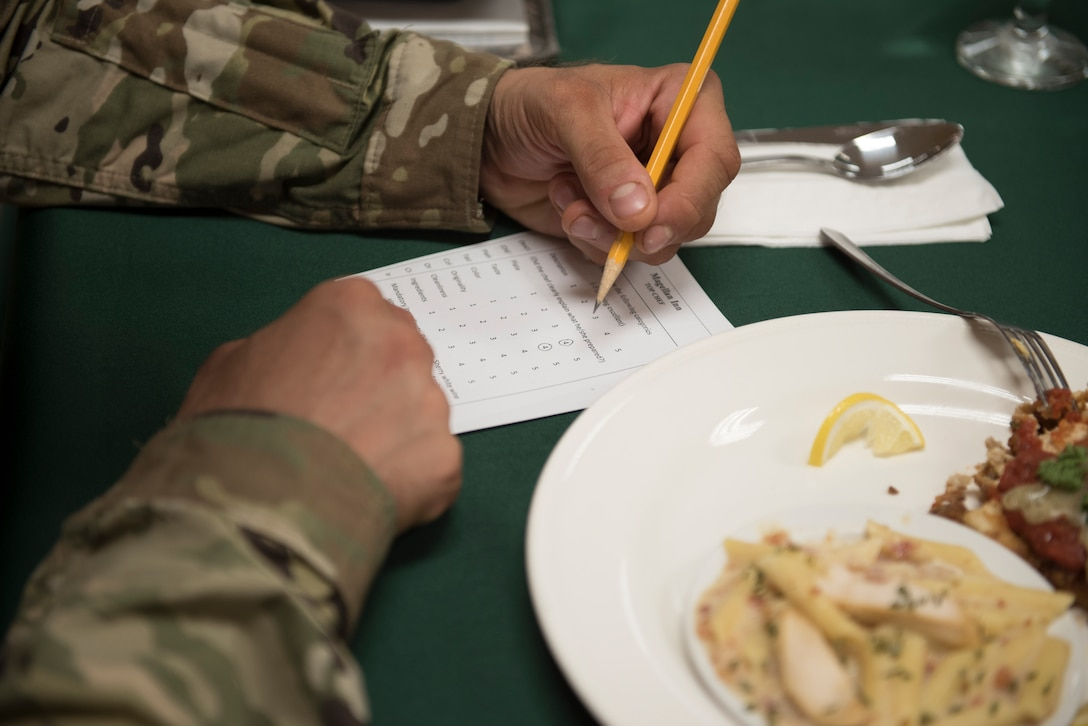 A U.S. Army culinary NCO grades a meal during a quarterly Top Chef competition March 8, 2018, at Andersen Air Force Base, Guam. Army and Air Force food services specialists assigned to Margellan Inn Dining Facility competed in a timed competition to prepare creative dishes with a selection of ingredients issued at the beginning of the competition. (U.S. Air Force photo by Staff Sgt. Alexander W. Riedel)