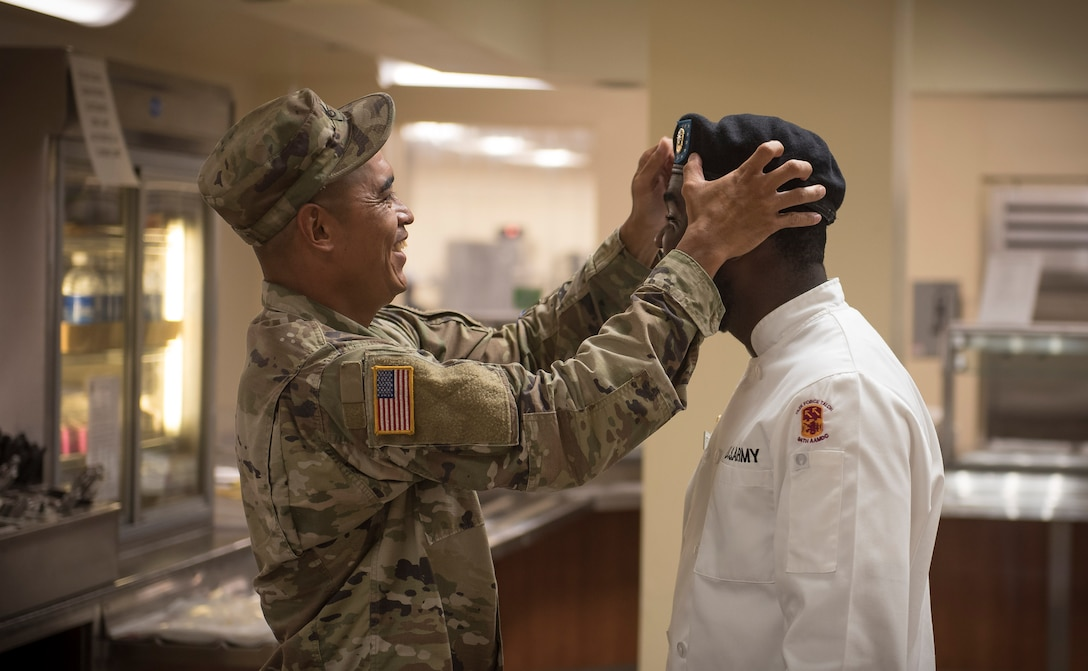U.S. Army Staff Sgt. Clarence Borja, left, adjusts the beret for Specialist Kevron Usher before the Soldier presents his food creation in front of a panel of judges during the quarterly Top Chef competition March 8, 2018, at Magellan Inn Dining Facility, Guam. Borja is a culinary NCO and Usher is a culinary specialist, both assigned to Task Force Talon's  E Battery, 3rd Air Defense Artillery Regiment. Soldiers are regularly attached to the U.S. Air Force's 36th Force Support Squadron in support of operations at Andersen Air Force Base. (U.S. Air Force photo by Staff Sgt. Alexander W. Riedel)