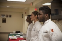 From the right, U.S. Army Specialist Kevron Usher, U.S. Air Force Senior Airman Caroline Spellen and Airman 1st Class Tyrell Jackson stand before a panel of judges during the quarterly Top Chef competition March 8, 2018, at Andersen Air Force Base, Guam. Magellan Inn dining facility hosts the quarterly competition to recognize its top culinary specialists and food services Airmen, and reward the Top Chef with a competitive internship at a local resort hotel. (U.S. Air Force photo by Staff Sgt. Alexander W. Riedel)