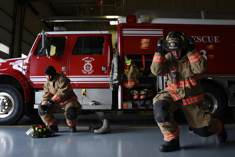 U.S. Air Force Airmen 1st Class Nicholas Denning, left, and Trevor Britt, 20th Civil Engineer Squadron firefighters, don their gear during a competition demonstrating their proficiency at Shaw Air Force Base, S.C., March 8, 2018. After receiving notification of an emergency, the Airmen must be prepared to depart the station and provide as quick of a response as possible. (U.S. Air Force photo by Airman 1st Class Kathryn R.C. Reaves)