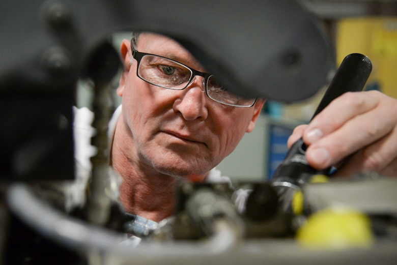 """Dave Duggar, 12th Maintenance Group J-85 propulsion shop supervisor, conducts an inspection on a T-38 Talon engine Feb. 28 2018, at Joint Base San Antonio-Randolph, Texas.  Duggar oversees the engine shop and test cell ensuring T-38 engines are """"mission ready"""" to conduct daily sorties for the 12th Flying Training Wing. (U.S. Air Force photo by Sean M. Worrell)"""