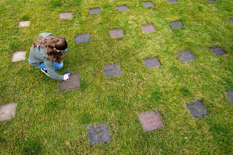 Cortlee Austin, Kaiserslautern Military Community member, cleans a gravestone at the American Kindergraves in Kaiserslautern, Germany, March 10, 2018. Between March and November, U.S. service members from the KMC area volunteer on a bi-weekly basis to maintain the Kindergraves by cleaning, mowing and placing flowers on graves. (U.S. Air Force photo by Senior Airman Devin Boyer)