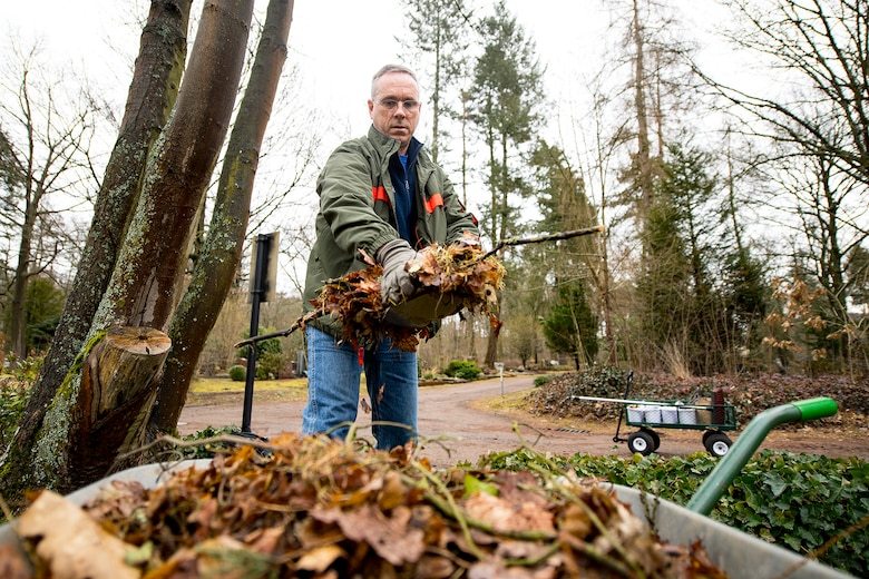 U.S. Air Force Chief Master Sgt. Philip Leonard, Ramstein Area Chief's Group member, transfers leaves into a wheel barrow while cleaning up the American Kindergraves in Kaiserslautern, Germany, March 10, 2018. The Ramstein Area Chief's Group has taken care of the Kindergraves with the German-American Women's Organization since the 1980s. (U.S. Air Force photo by Senior Airman Devin Boyer)