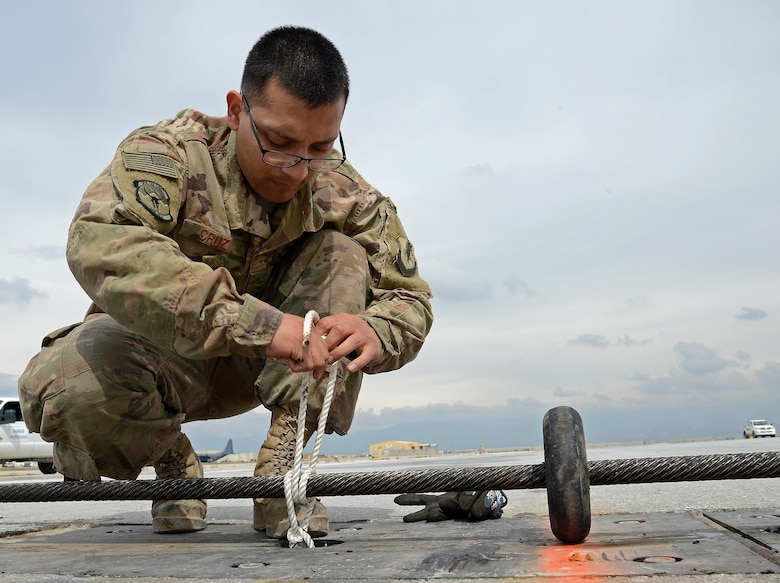 Airman Rene Cruz, 455th Expeditionary Civil Engineer Squadron power production engineer, ties down part of the Aircraft Arrest System Mar. 3, 2018 at Bagram Airfield, Afghanistan.