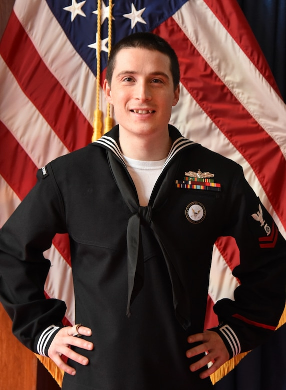 A Navy Chief Petty Officer stands in front of American flags.