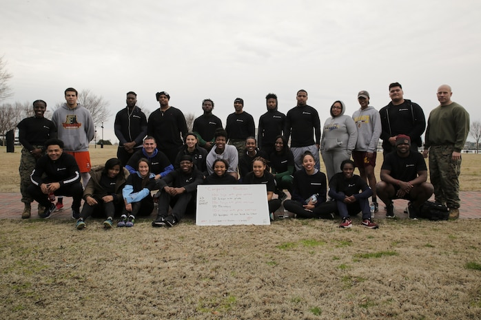 Student-Athletes of the 2018 Mid-Eastern Athletic Conference pose for a photo with Capt. Charlyne Delus (left) and First Sgt. Nicolas Imperial (right) after completing a morning workout honoring Cpl. Jason Dunham at Town Point Park in Norfolk, Virginia, March 10. The workout was chosen by First Sgt. Imperial to teach the participants about their character and fighting spirit. Dunham was posthumously awarded the Medal of Honor for his actions while serving with 3rd Battalion, 7th Marines during the Iraq War. Delus is a manpower officer with Manpower and Reserve Affairs. Imperial is the inspector instructor first sergeant for 4th Assault Amphibian Battalion, 4th Marine Division, Marine Forces Reserve.