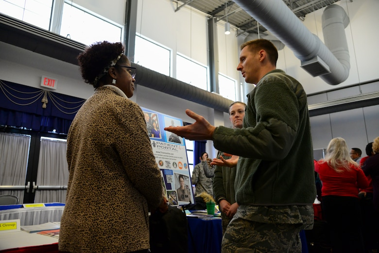 Trina Brown-Hicks, Humana, speaks with Maj. Nick Freese, 436th Medical Group practice manager, and Airman 1st Class Morgan Stanfield, 436th Medical Group medical records technician, during the second annual Spouse Symposium March 7, 2018, at Dover Air Force Base, Del. Representatives of the 436th MDG, Military One Source, the USO and several other base organizations set up booths at the career information fair during the event to help inform spouses of the support provided by the installation. (U.S. Air Force photo by Staff Sgt. Aaron J. Jenne)