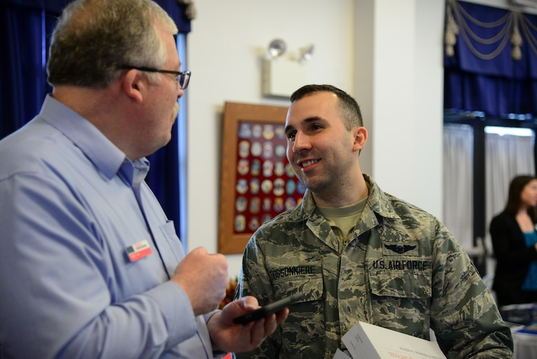 Roger Saul, Military One Source, speaks with Airman 1st Class Jonathan Teissonniere, 9th Airlift Squadron loadmaster, about several job opportunities for his spouse during the career information fair segment of the second annual Spouse Symposium March 7, 2018, at Dover Air Force Base, Del. Spouses of active duty and reserve Airmen were invited to attend the free event. (U.S. Air Force photo by Staff Sgt. Aaron J. Jenne)