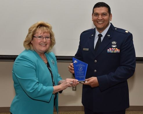 Cynthia Abbott, the director of Logistics and Logistics Services presents Major Jose Perez IV with a Logistics award. Perez was one of many individuals honored for outstanding achievement. (U.S. Air Force photo / Michelle Gigante)