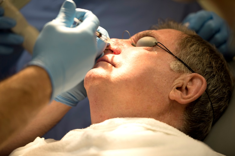 Maj. (Dr.) Thomas Beachkofsky, dermatology element leader assigned to the 6th Medical Group, injects lidocaine into the nose of a dermatology patient, to numb the surrounding area during a laser treatment at MacDill Air Force Base, Fla., March 9, 2018.