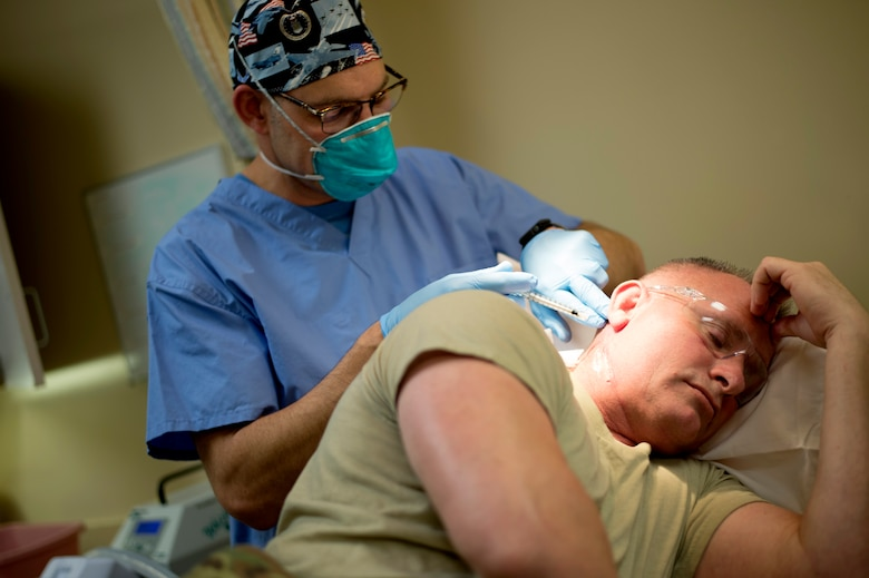 Maj. (Dr.) Thomas Beachkofsky, dermatology element leader assigned to the 6th Medical Group, puts a liquid medication on a dermatology patient after a laser treatment at MacDill Air Force Base, Fla., March 9, 2018.