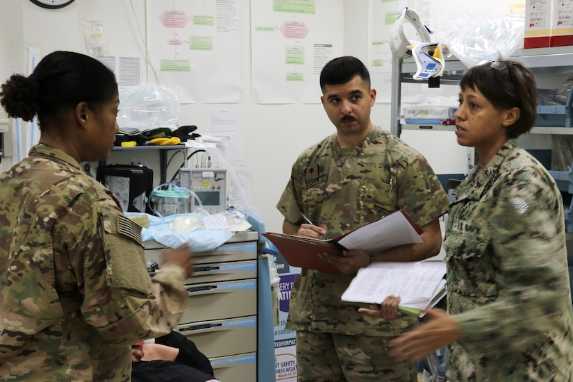 Navy Cmdr. Christina Cabradillia, a clinical operations officer, Combined Joint Task Force – Operation Inherent Resolve, coaches other medical personnel at the Camp Arifjan, Kuwait, troop medical center during a mass casualty exercise, March 7, 2018. The exercise tested first responders and other emergency services that would be crucial during a real-world emergency.
