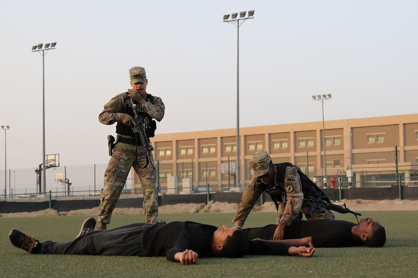 Specialist Jeremiah Matthews checks a simulated shooter for weapons while Pfc. Christian Ibarra uses his radio to report updates during an active shooter and mass casualty drill, Camp Arifjan, Kuwait, March 7, 2018. The exercise tested first responders and other emergency services that would be crucial during a real-world emergency.