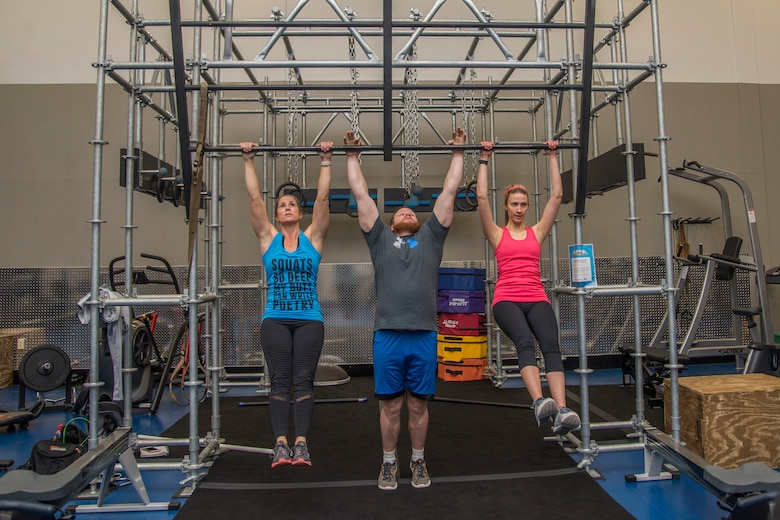 Stefanie Tucker, Steven Tucker, and Jamie Knight perform pull-ups on the newly installed Alpha Warrior Battle Rig Feb. 26, 2018, at Scott Air Force Base, Ill. The battle rig encompasses the four pillars of Comprehensive Airmen Fitness: physical, social, spiritual and mental fitness. (U.S. Air Force photo by Senior Airman Melissa Estevez)
