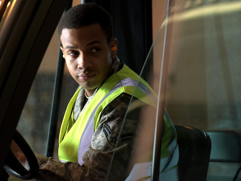 U.S. Air Force Airman 1st Class Daniel Johnson, 100th Logistics Readiness Squadron traffic management officer, checks to make sure the area is clear before reversing his forklift during a cargo deployment function at RAF Mildenhall, England, March 9, 2018. The CDF involved moving almost 10,000 pounds of equipment to Camp Lemonier, Djibouti. (U.S. Air Force photo by Airman 1st Class Benjamin Cooper)