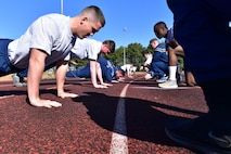 Airmen do push-ups, while other Airmen kneel in front of them.
