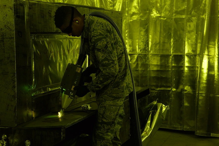 Airman 1st Class Levi Gordon, 60th Maintenance Squadron aircraft structural maintenance, uses a Clean Laser 1000 to remove paint from a sheet of metal March 7 at Travis Air Force Base, California. The 1000-watt laser can remove paint and corrosion. It reduces the waste created from sanding paint by 90 percent Travis was chosen as one of two bases to test the capabilities of the laser. (U.S. Air Force photos by Staff Sgt. Amber Carter)