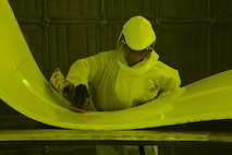 Kathy Fruits, 60th Maintenance Squadron aircraft structural maintenance, uses a sander to remove paint March 7 at Travis Air Force Base, Calif. The suit is completely air sealed and hooked up to oxygen in order to protect her from harmful paint chemicals that are released during the sanding process. The suit is not needed while using the Clean Laser due to the reduction of sawdust and airborn debris. (U.S. Air Force photo by Staff Sgt. Amber Carter)