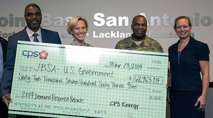 Garrick Williams (left), JBSA Energy Solutions director with CPS Energy, presents (from left) Brig. Gen. Heather Pringle (right), 502nd Air Base Wing and Joint Base San Antonio commander, Col. Lee Flemming, 502nd ABW and JBSA vice commander, and Brenda Roesch, 502nd Civil Engineer Squadron director, a rebate check for $62,763.04 at the 502nd ABW headquarters at JBSA-Fort Sam Houston March 13.