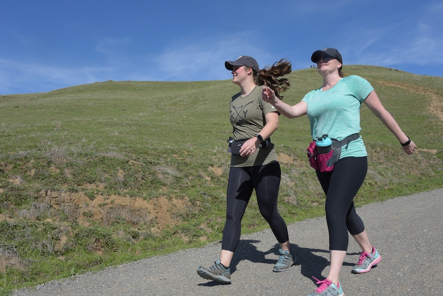Tech. Sgt. Nikki Webb (Left), 60th Air Mobility Wing, hikes down a hill at Pena Adobe Regional Park in Vacaville, Calif., with her cousin, Senior Master Sgt. Jenny Hendry (Right), 60th Aeromedical Squadron, March 11, 2018. Hendry joined Webb on a 10-mile hike as she prepares for the Bataan Memorial Death March on March 25. (U.S. Air Force photo/Tech. Sgt. James Hodgman)