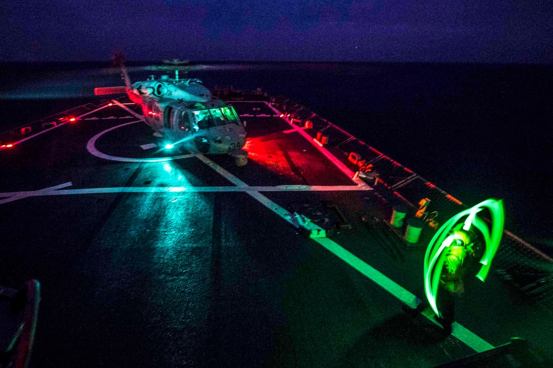 A sailor signals to a helicopter on a ship at night.