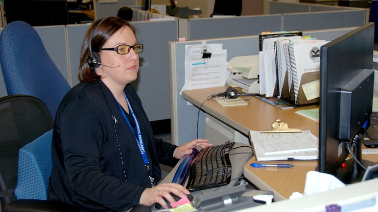 A customer service agent works on a computer