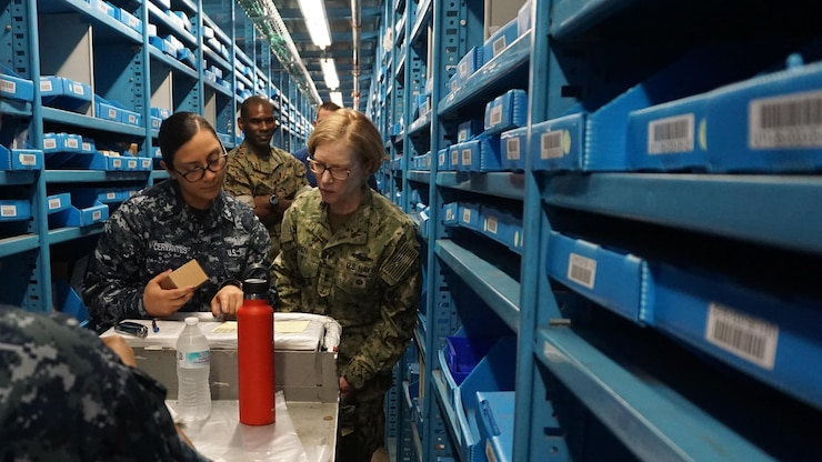 Service members look at parts while surrounded by bins in a warehouse