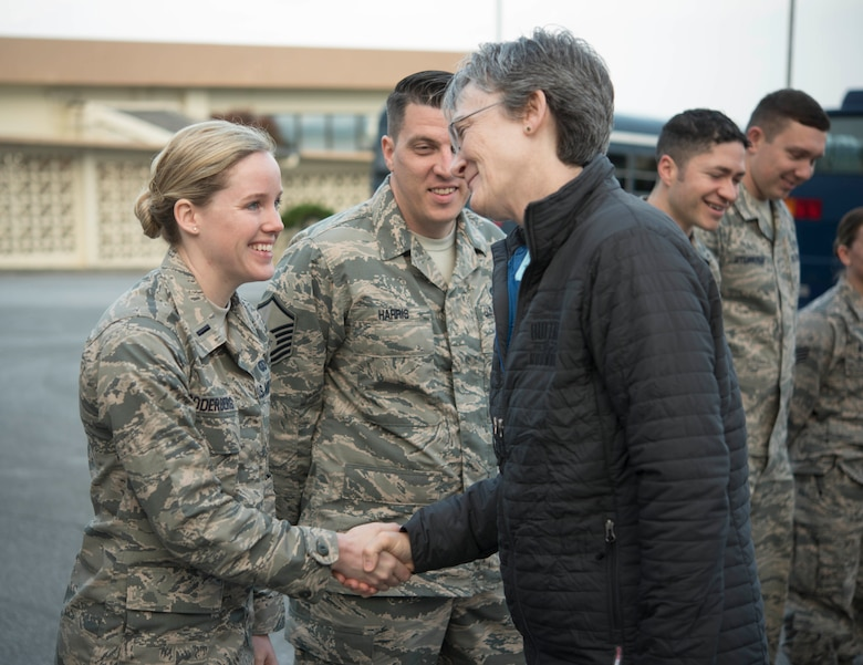 Secretary of the Air Force Heather Wilson (right) coins 1st Lt. Laura Soderberg, 18th Wing protocol officer in charge, Feb. 2, 2018, at Kadena Air Base, Japan. Challenge coins are a military tradition in which a senior military leader or a member of a distinguished office acknowledges the awards, accomplishments or significant acts of a particular service member.
