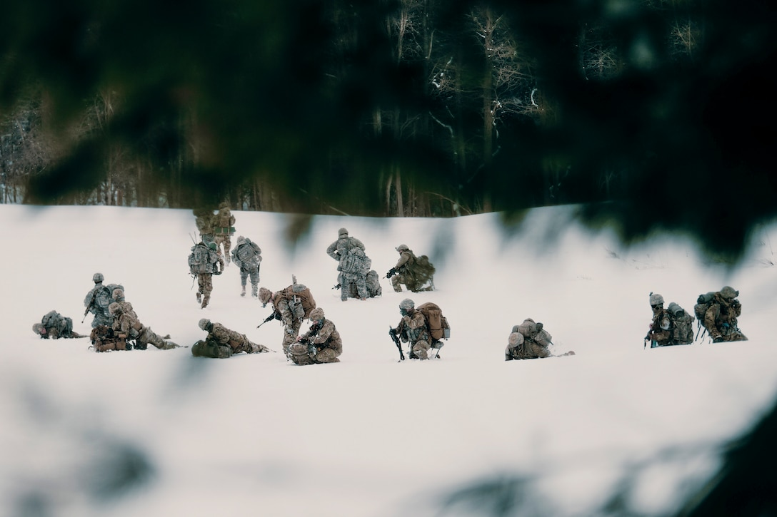 More than a dozen soldiers framed by tree branches set up security in the snow.