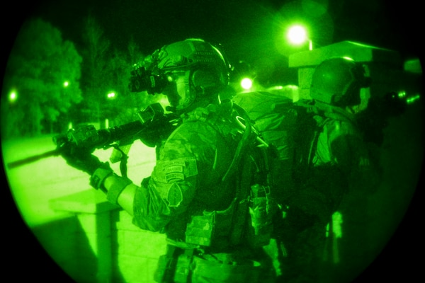 As seen through a night-vision device, soldiers and members of NATO forces perform close quarters battle training at Camp Shelby, Miss., March 5, 2018, to support Emerald Warrior. During the exercise, U.S. Special Operations Command forces train to respond to various threats across the spectrum of conflict. Air Force photo by Airman 1st Class Kristen Heller