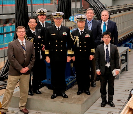 IMAGE: DAHLGREN, Va. (Feb. 16, 2018) - Japanese Vice Adm. Hideki Yuasa and Capt. Takuro Koroki are pictured with their delegation and Naval Surface Warfare Center Dahlgren Division (NSWCDD) leadership in front of the electromagnetic railgun prototype launcher. Yuasa is president of the Japan Maritime Self-Defense Force (JMSDF) Maritime Command and Staff College in Tokyo and Koroki is the naval attaché for the Embassy of Japan and the JMSDF delegation. Yuasa led the Japanese delegation to see new and emerging technologies developed at NSWCDD. Navy scientists and engineers briefed the Japanese delegation on human systems integration, electromagnetic launchers, hypervelocity projectiles, and directed energy weapons, in addition to the command's capabilities in complex warfare systems development and integration to incorporate electric weapons technology into existing and future fighting forces and platforms. (U.S. Navy photo/Released)
