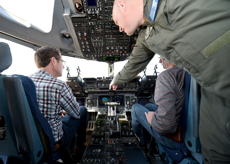 U.S. Air Force Lt. Col. James Akers, a C-17 Globemaster III flight commander assigned to the 730th Air Mobility Training Squadron, shows two civilian pilots some of the instruments a C-17, March 10, 2018, at Altus Air Force Base, Okla.