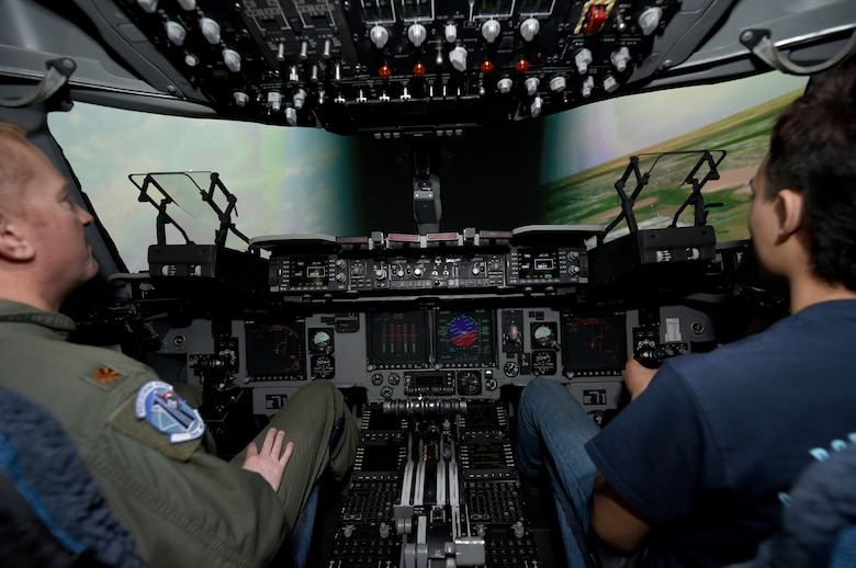 U.S. Air Force Maj Jon Paul Griffin, a C-17 Globemaster III flight training instructor assigned to the 730 Air Mobility Training Squadron, flies a simulator with a civilian pilot in training, March 10, 2018, at Altus Air Force Base, Okla.