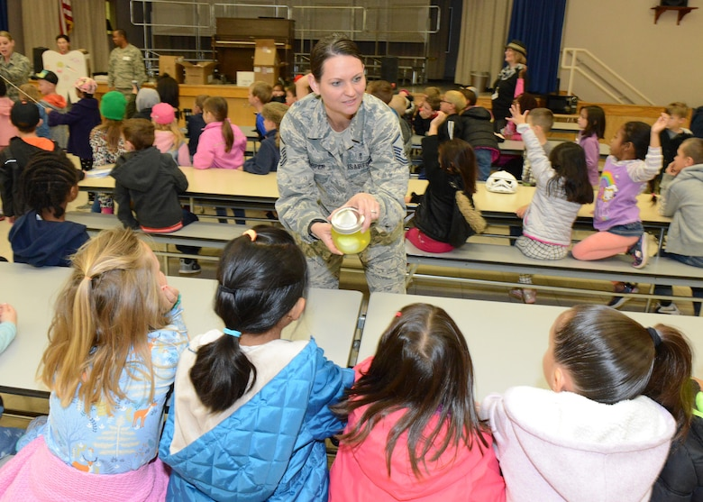 Master Sgt. Christina Harper, 412th Aerospace Medicine Squadron Dental Flight chief, shows Branch Elementary School students an egg submerged in soda to demonstrate how sugar can break down tooth enamel if not properly cleaned. February is National Children's Dental Health Month. (U.S. Air Force photo by Kenji Thuloweit)