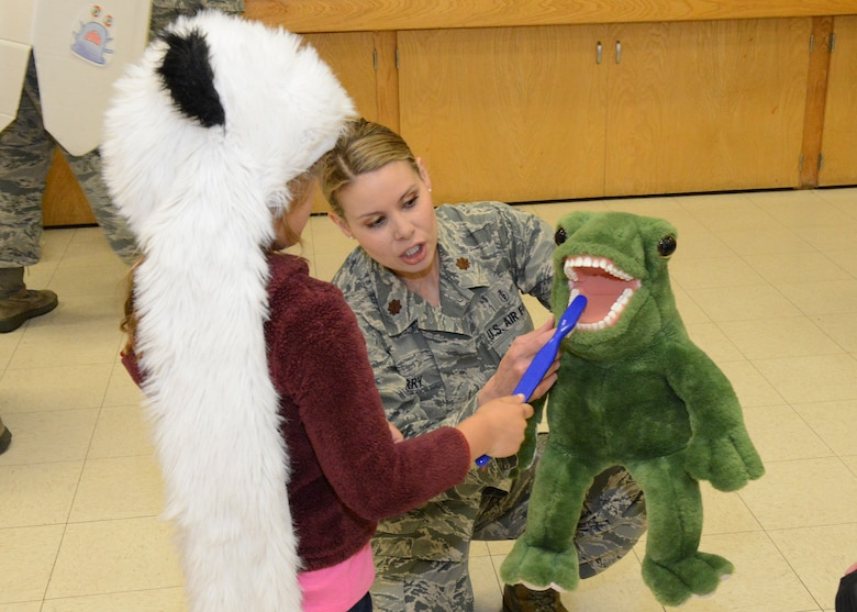 Maj. Tonya Barry, 412th Aerospace Medicine Squadron, shows a Branch Elementary School first grader how to brush teeth properly during a visit to the school March 1. February is National Children's Dental Health Month. (U.S. Air Force photo by Kenji Thuloweit)