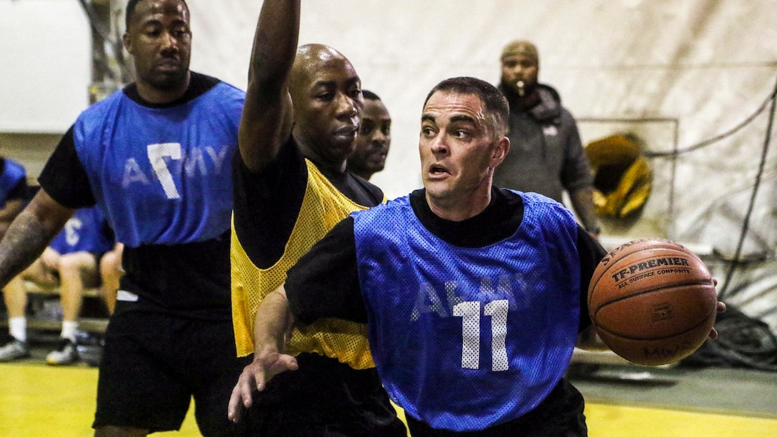 A soldiers holds a basketball in one hand as he contemplates his next move during a game.