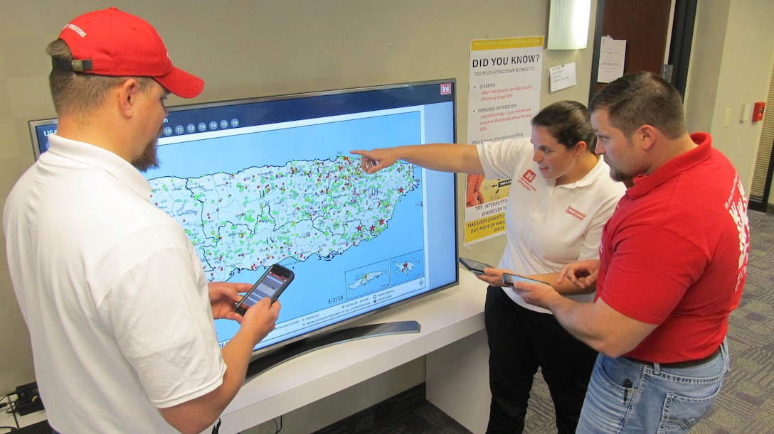 U.S. Army Corps of Engineers employees Bill Spring, (left) Jake Ellison, (middle) and Kara Hickey, Geographic Information Systems Analyst and mission liaisons for the Task Force Temporary Emergency Power Team discuss issues as they fine-tune an app that was created by the team on March 2, 2018 in San Juan Puerto Rico.  The app tracks approving official signatures and checklist of commissioned and decommissioned micro grids.