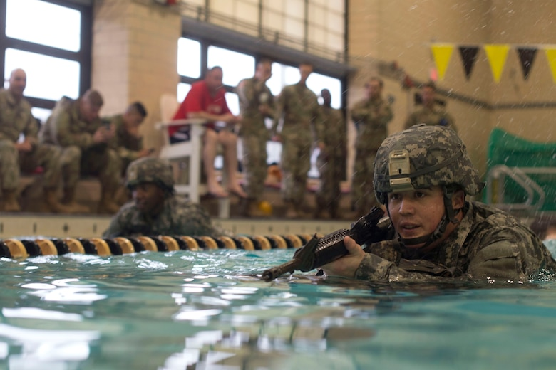 U.S. Army Sgt. Ian Lubert, 689th Rapid Port Opening Element, 832nd Transportation Battalion, 597th Transportation Brigade cargo specialist, swims in full gear at Anderson Field House at Joint Base Langley-Eustis, Virginia, March 1, 2018. The competition was part of the brigade's week-long Rapid Support Challenge. (U.S. Air Force photo by Airman 1st Class Monica Roybal)