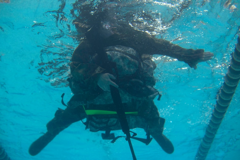 A U.S. Army Soldier swims while wearing full gear at Anderson Field House at Joint Base Langley-Eustis, Virginia, March 1, 2018. Soldiers were tasked with swimming 50 meters while carrying a weapon and a 30-pound ruck. (U.S. Air Force photo by Monica Roybal)