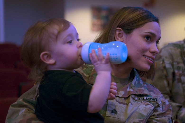 U.S. Army Sgt. Austiana Lubert, 690th Rapid Port Opening, 832nd Transportation Battatlion, 597th Transportation Brigade transportation management coordinator, holds her son Wyatt, age 1, during an awards ceremony in Wylie Theater at Joint Base Langley-Eustis, Virginia, March 1, 2018. Austiana supported her husband U.S. Army Sgt. Ian Lubert, 689th Rapid Port Opening Element, 832nd Transportation Battalion, 597th Transportation Brigade cargo specialist, throughout the brigade's Rapid Support Challenge. (U.S. Air Force photo by Monica Roybal)