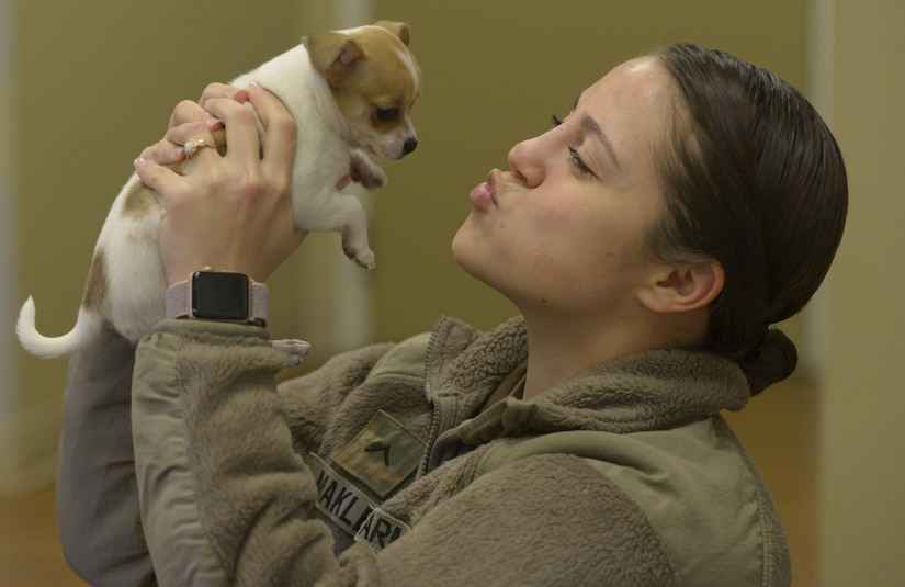 U.S. Army Pvt. Aeris Makley, Public Health Activity, Fort Gordon, animal care specialist, shows compassion to a puppy visiting the Veterinarian Clinic here March 9, 2018.