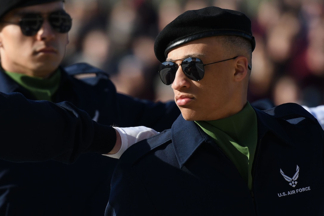 """U.S. Air Force Airman Basic Jeffrey Guillory, 334th Training Squadron regulation drill team member, performs during the 81st Training Group drill down on the Levitow Training Support Facility drill pad March 9, 2018, on Keesler Air Force Base, Mississippi. Airmen from the 81st TRG competed in a quarterly open ranks inspection, regulation drill routine and freestyle drill routine. The 335th TRS """"Bulls"""" took first place this quarter. (U.S. Air Force photo by Kemberly Groue)"""