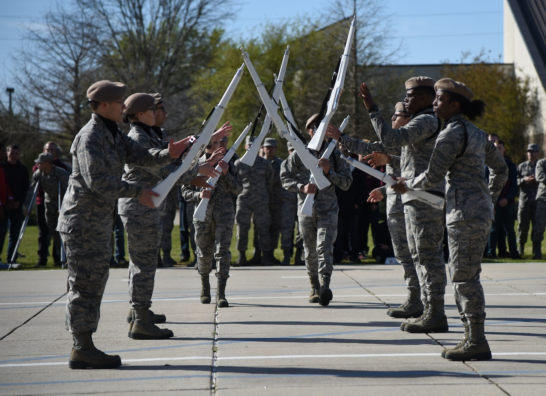 "Members of the 335th Training Squadron freestyle drill team drill master, spin their rifles during the 81st Training Group drill down on the Levitow Training Support Facility drill pad March 9, 2018, on Keesler Air Force Base, Mississippi. Airmen from the 81st TRG competed in a quarterly open ranks inspection, regulation drill routine and freestyle drill routine. The 335th TRS ""Bulls"" took first place this quarter. (U.S. Air Force photo by Kemberly Groue)"