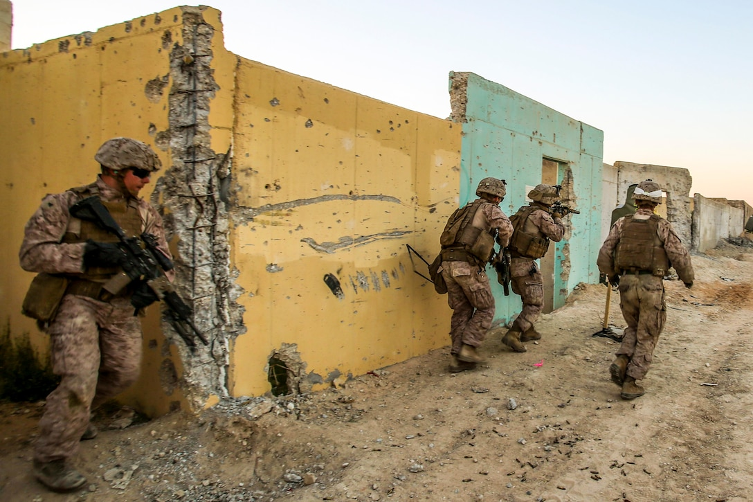 Marines conduct a live-fire exercise next to yellow and turquoise building during an exercise in Israel.