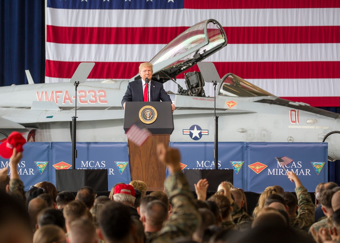 President Donald J. Trump speaks to troops from behind a podium.