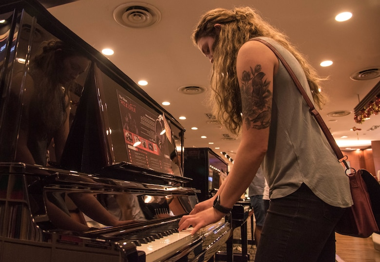 U.S. Air Force Senior Airman Emily Wall, a Pacific Air Forces' F-16 Demonstration Team crew chief, plays a piano at Changi, Singapore, Feb. 2, 2018. Wall enjoyed dabbling in many different hobbies growing up, piano being one of her favorites. Wall enlisted in the Air Force to try a more challenging path to facilitate character growth in her life. (U.S. Air Force photo by Senior Airman Sadie Colbert)